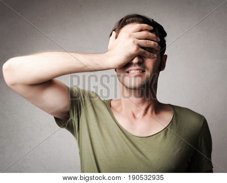 Scatterbrained man covering his faced with one hand