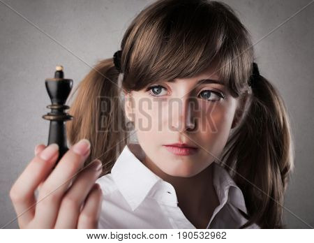 Teenager holding a chess piece