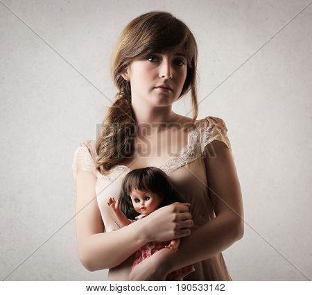 Emotionless young woman holding tight a doll