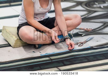 the woman sewing scenery for a theatrical performance. theatrical sceneries, handmade concept. the artist makes scenery for theater close up.
