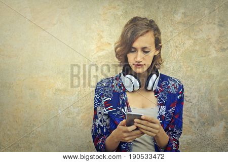 Teenager with headphones using a smartphone