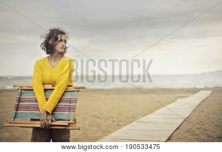 Young woman standing at the beach on a windy day