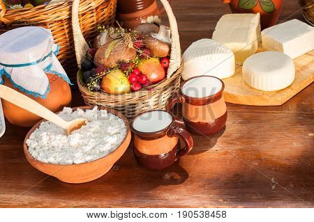 Dairy farm products on wooden table. Cheese and milk on the table in an earthenware dish. Rustic, organic food, farm products concept. Food background.