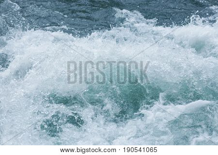 splashes of blue sea waves close up. Churning blue water in the ocean shows lots of turbulence and splash. freshness, wave, surfing concept. elements of water.