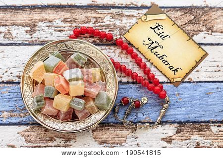 Eid mubarak text on the card with red rosary and turkish delights on the vintage table poster