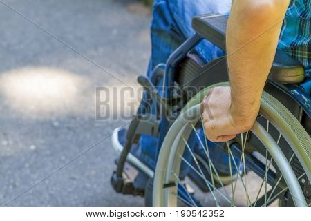 Hand of young man on the wheel of wheelchair in the city park.