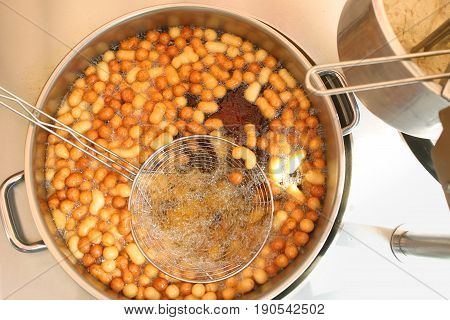 Sweet mini donuts frying in donuts machine. Pot with mini donuts and colander frying  in oil.
