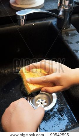 Child Washing Dishes. A young child's hands wash dishes over a sink in an authentic kitchen scene