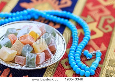 Turkish delights in plate on the traditional turkish carpet with blue rosary poster