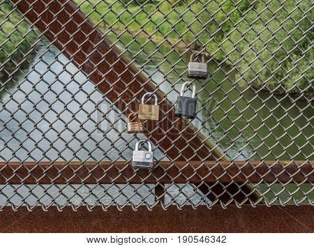 Love locks are attached to a fence on a bridge with the Green River below.