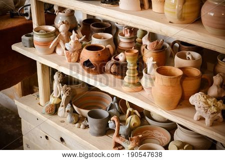 Wooden racks in a pottery workshop in which there are pottery, many different pottery standing on the shelves in a potery workshop. Low light
