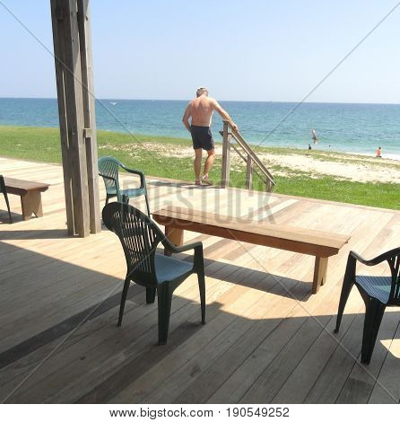 Male senior relaxing outdoors on the beach alone.