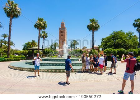 Marrakech Morocco - May 12 2017: A group of tourists taking photos of each other in front of the fountain in Koutoubia Gardens with the Koutoubia Mosque in the background.