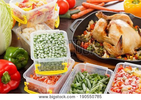 Frozen veggies nutrition in plastic containers roasted chicken in pan. Healthy freezer food.