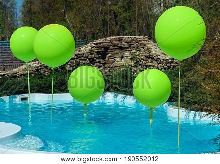 Pool With Big Green Balloons Outdoor. Poolside Party. The Balloons On Water. Decorations For Wedding