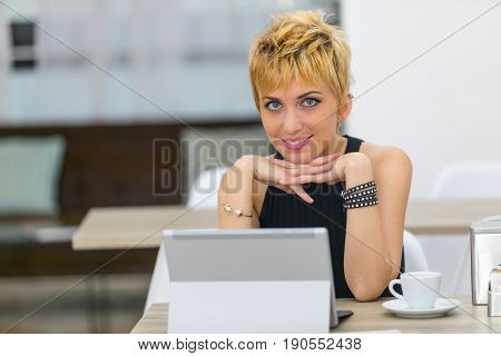 Smiling Businesswoman Sat At Desk With Computer