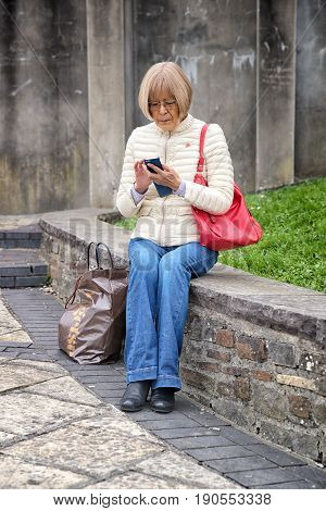 Elderly Lady Sat On Wall Using Her Smartphone With Her Shopping