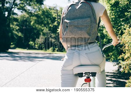 Slender Girl In A White T-shirt, Jeans And With A Backpack Sits On Her City Bike In The Park