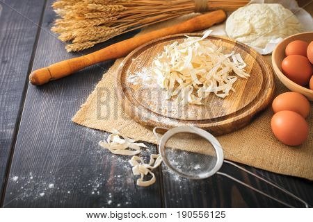 Fresh homemade pasta with pasta ingredients on the dark wooden table.