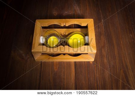 The wooden retro sand glass clock lie on side with sand on wooden background. time stop concept.
