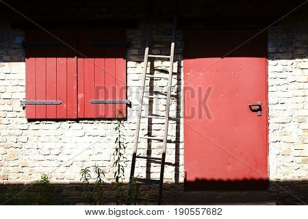 A ladder leaning against a barn in the sunlight with a wooden door and a closed window.