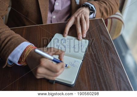 Businessman hands with pen writing notebook on office desk table close up. Business concept