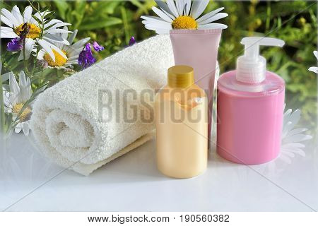 Natural hypoallergenic herbal Cosmetic products for skin care: plastic dispenser with liquid soap bottle of lotion tube of cream and white terry cotton towel on a camomile flowers background