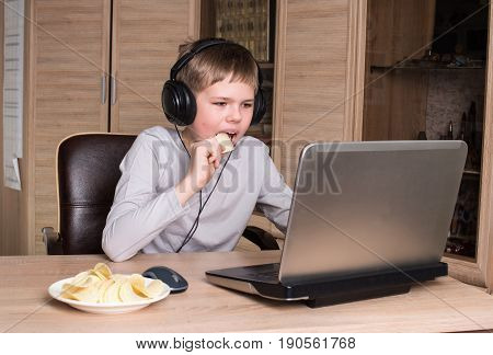 Kid in headphones eating chips while using pc in his room. Boy eating potatoes chips and surfing on internet or playing video games on laptop.
