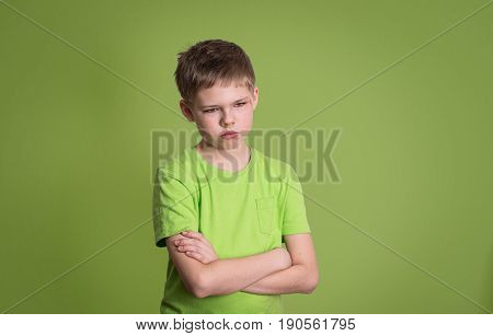 Upset unhappy angry kid with arms crossed scratch on his face isolated on green background.