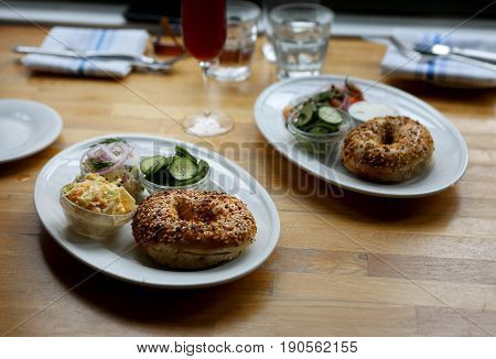 Platters with cream cheese, bagels, coleslaw, cucumber salad and white fish salad on restaurant table setting