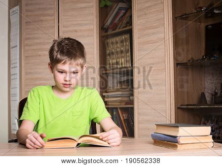 Education and school concept. Surprised boy student reading a book in his room.
