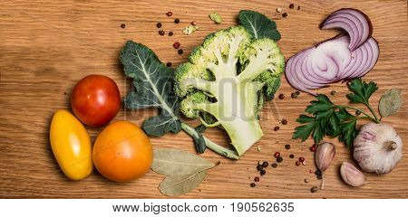 Bunch of fresh green broccoli on wooden background. Fresh broccoli cut into halves with ingredients for cooking close up. Vegan food vegetarian and healthily cooking concept.