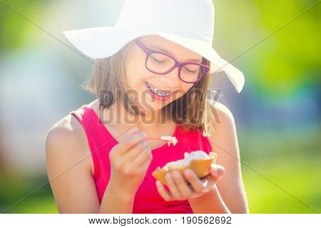 Cheerful teenage girl with dental braces glasses and ice cream. Portrait of a smiling pretty young girl in summer outfit with ice cream and teeth braces.