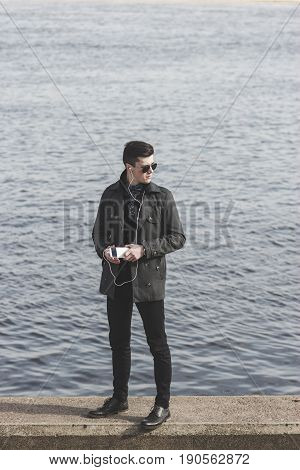 handsome young man in sunglasses listening to music near water