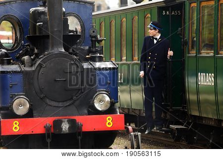 Mariefred Sweden - May 11 2013: The train conductor is on the footstep of the passenger car next to steam locomotive number 8 Emsfors at the railway museum station in Mariefred.