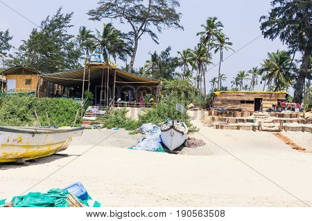 View Of A Tropical Sandy Beach With Bungalows And Boats On A Background Of Palms.
