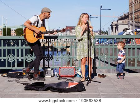 Stockholm Sweden - August 19 2015: Two street musicians on the bridge Stallbron in Stockholm with an interested little boy from the audience.