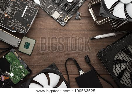 central processing unit and other computer parts on the brown table. computer parts on wooden table. computer parts background with copy space. building personal gaming and video production computer concept. custom computer build