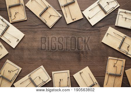 many mousetraps frame with copy space. mousetraps on the brown table. background with wooden mousetraps. lots of mousetraps background