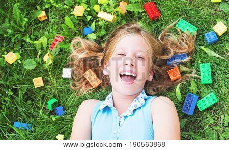 Happy child girl laughing and playing with toys constructor plastic blocks on the grass.