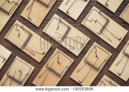many mousetraps in order. mousetraps on the brown table. background with wooden mousetraps. lots of mousetraps background
