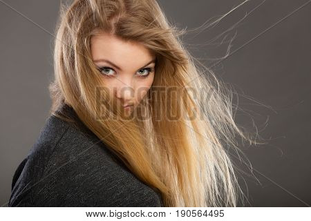 Haircare beauty hairstyling concept. Portrait of young attractive blonde woman wearing dark t shirt having windblown beautiful long hair.
