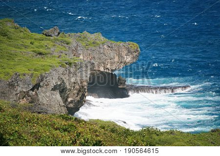 jutting rocks above the blue ocean  Rock formation showing a jutting point just above a rock platform in the ocean