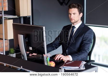 Involved in work. Portrait of serious elegant young man is typing on keyboard while looking at screen of computer with concentration