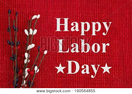 Happy Labor Day text on red white and blue pip floral berry spray on a shiny red material with copy space for your message