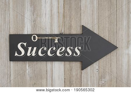 Success text on arrow chalkboard sign with a skeleton key on weathered wood