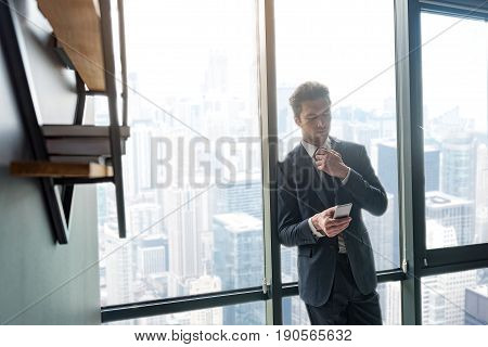 Hard decision. Young attractive man is looking at screen of his phone and expressing concern while leaning on window. Copy space in the left side