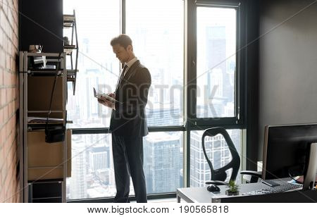 Great book. Pleasant thoughtful managing director is reading while standing in office against window. Copy space in the right side