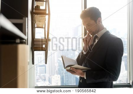 Involved in reading. Confident young businessman is perusing book and touching his chin thoughtfully while standing against window