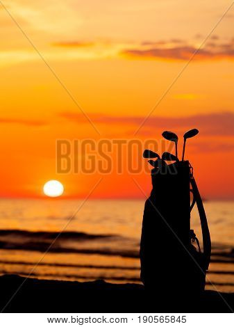 Idyllic shot of sunset by the sea waters warm orange and red colors and bag with golf club equipment